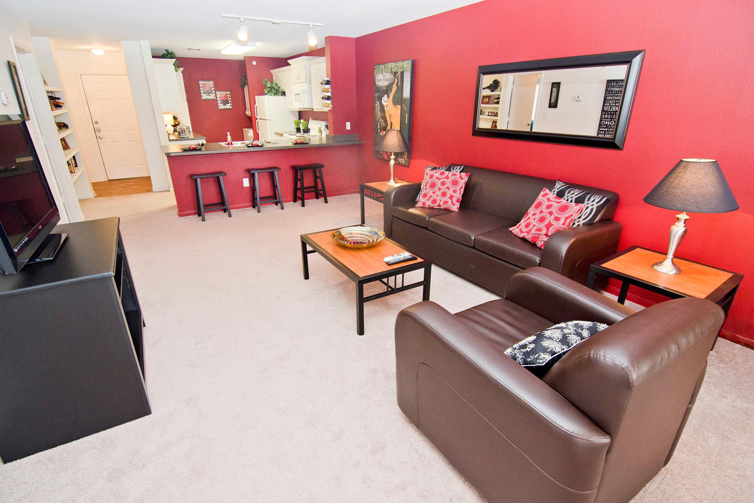 a living room filled with furniture and a red leather chair
