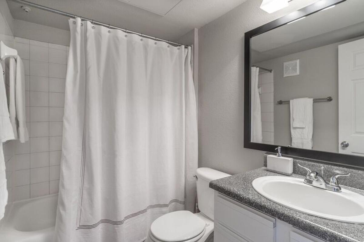 a white sink and shower curtain