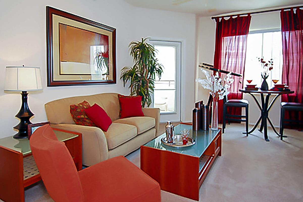 a living room filled with furniture and a red chair