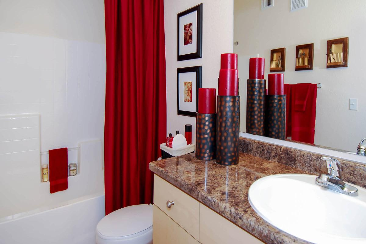a red and white sink and a mirror