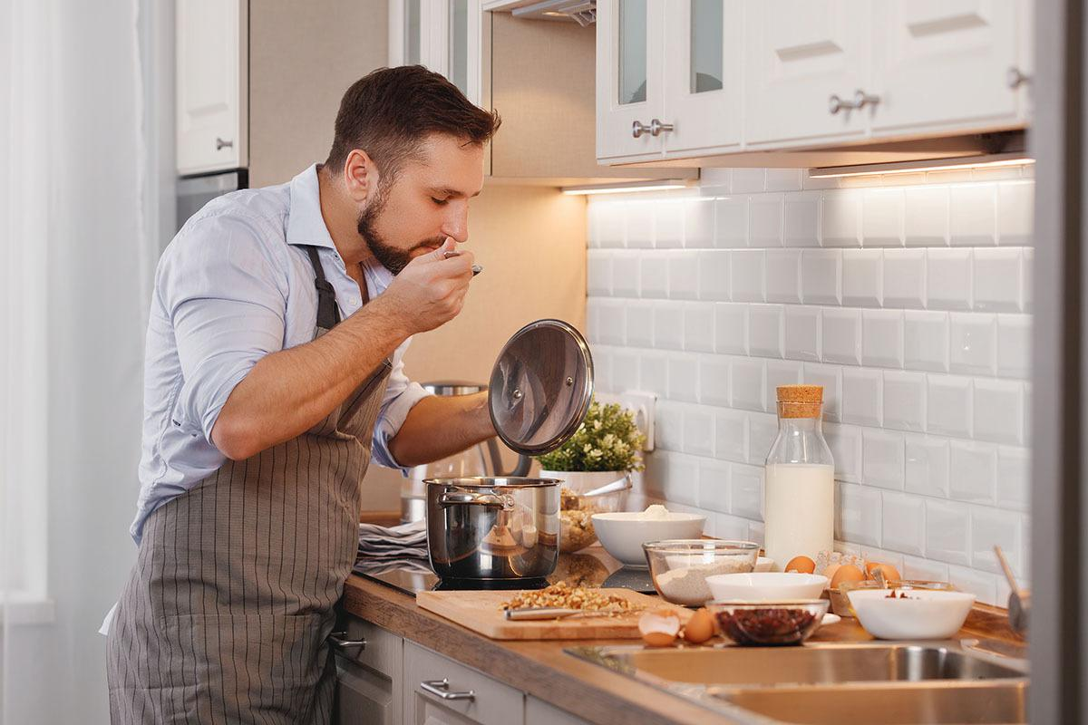 a man standing in a kitchen preparing food