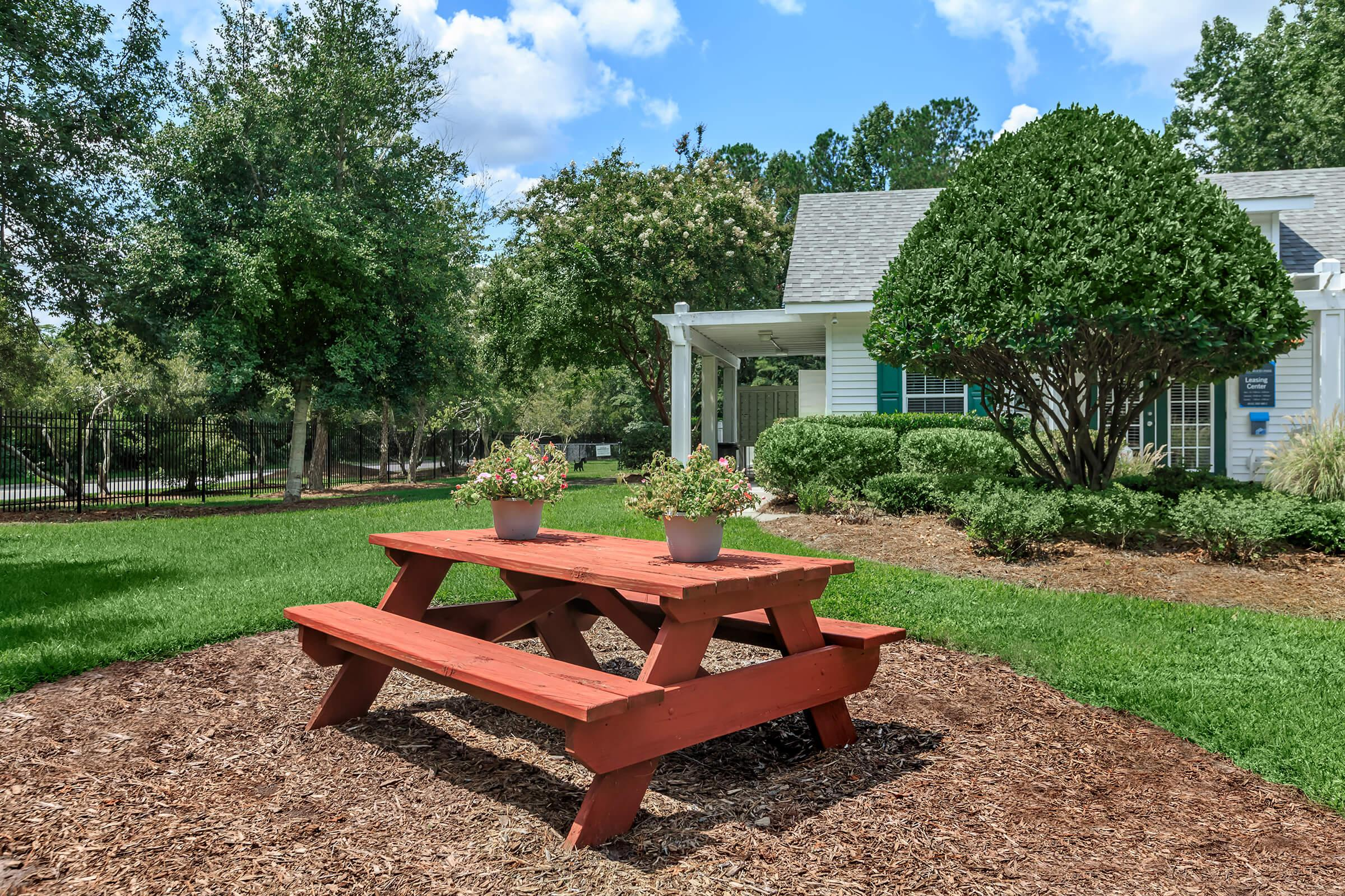 an empty park bench next to a picnic table