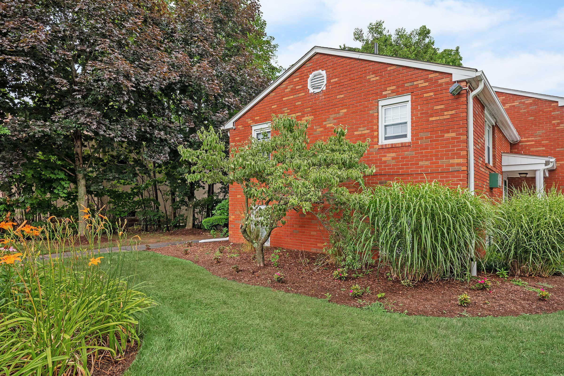 a large brick building with grass in front of a house