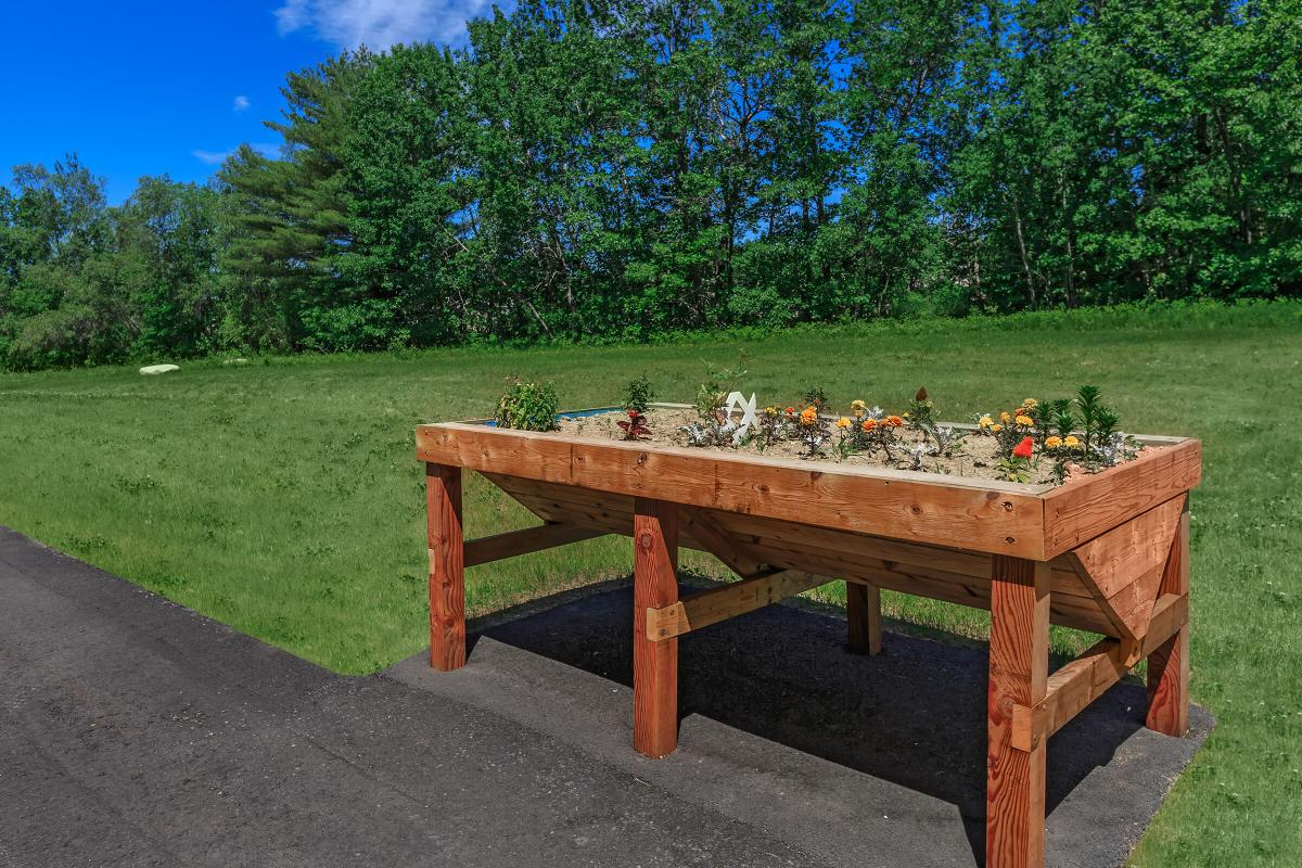 a wooden bench sitting in front of a picnic table
