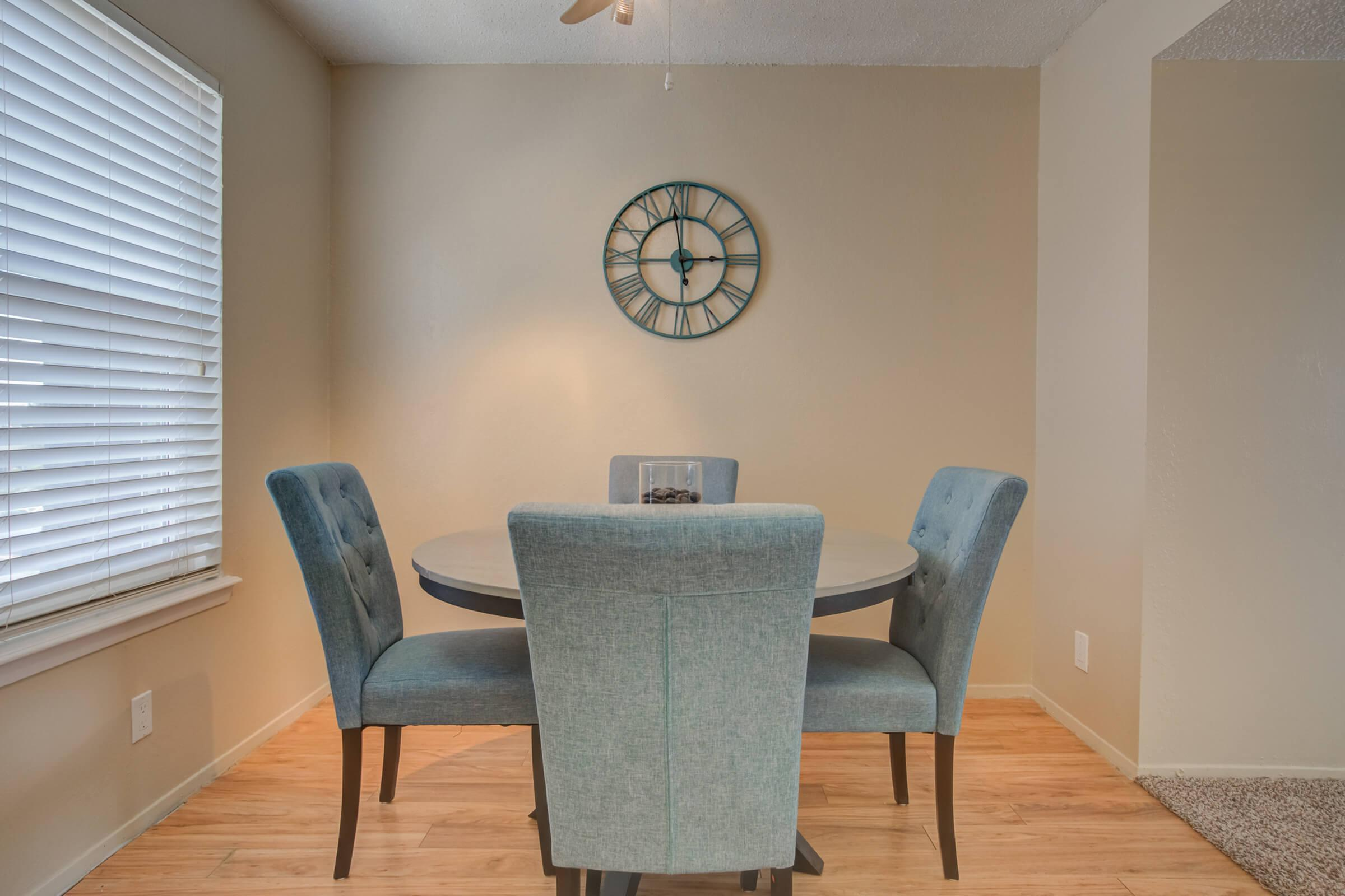 a living room with a clock at the top of a wooden chair