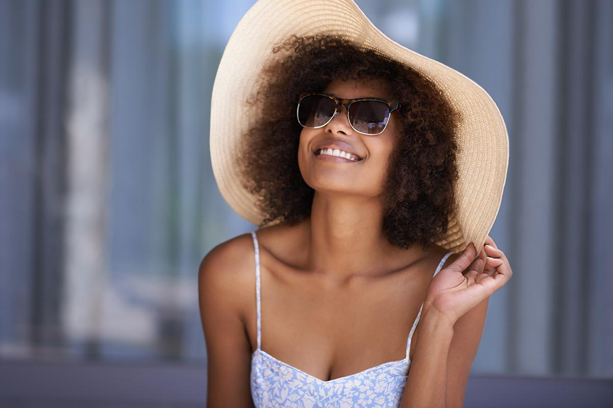 a person wearing a hat and sunglasses posing for the camera