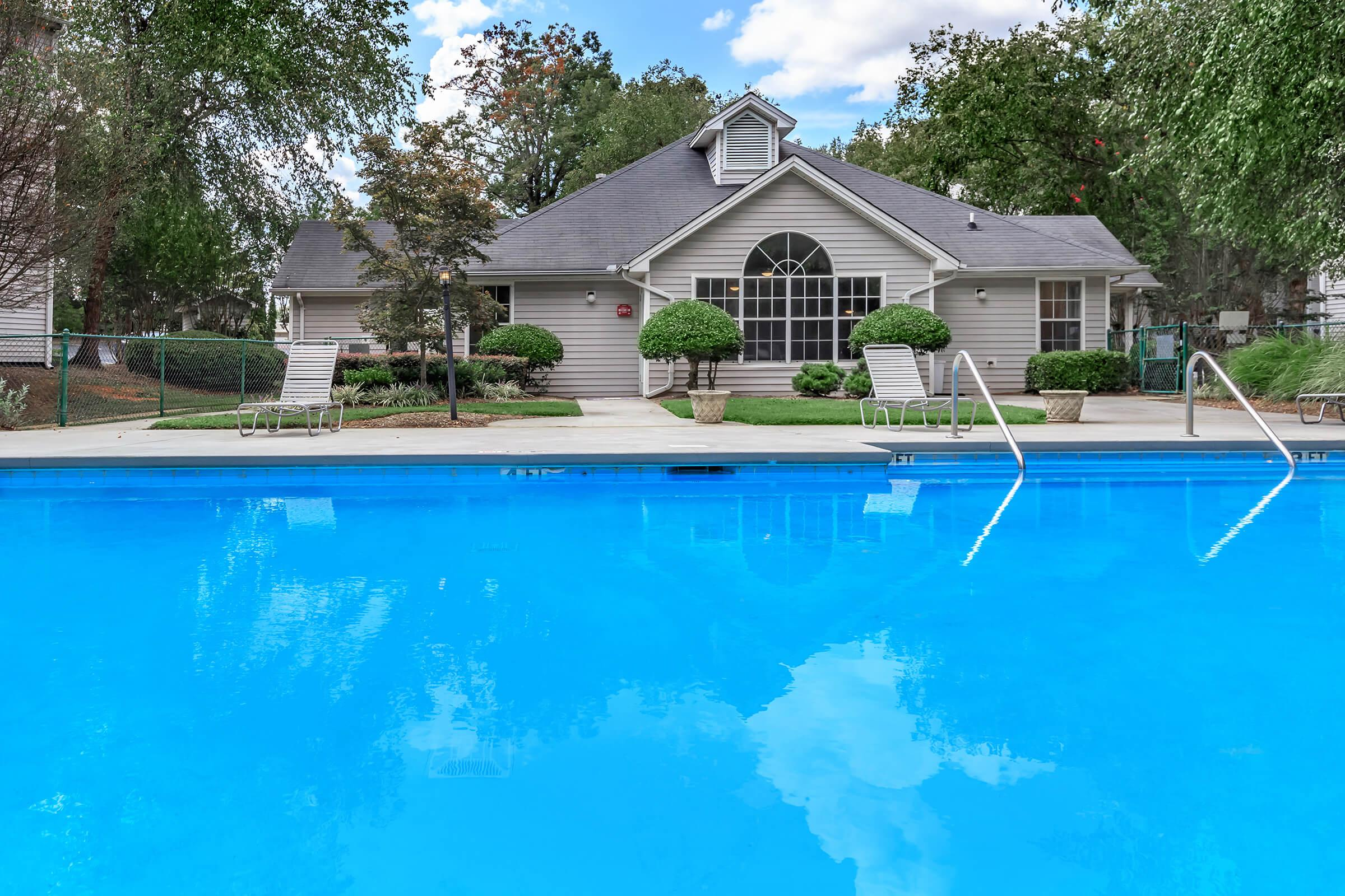 a blue pool of water in front of a house