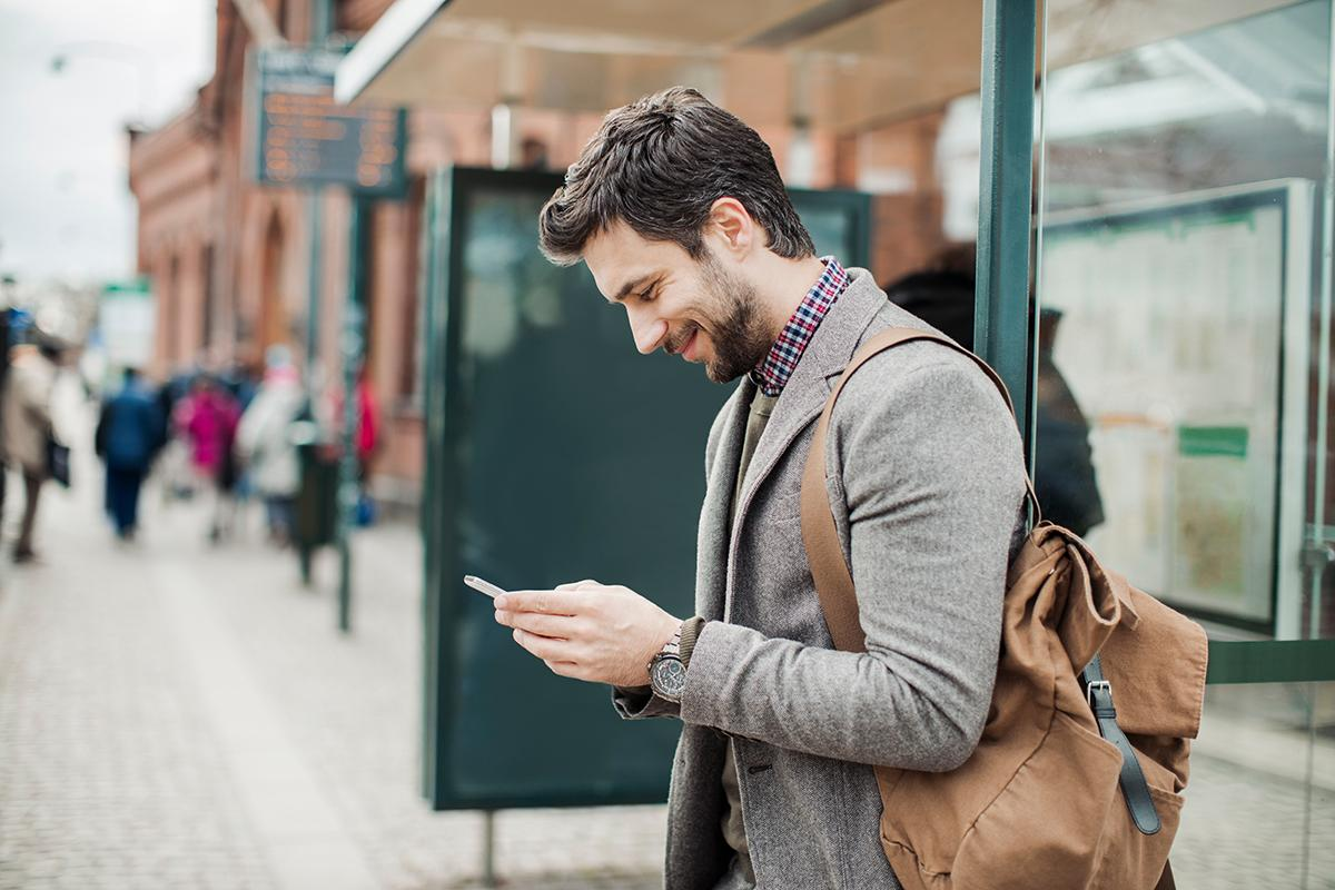 a man standing on the sidewalk talking on a cell phone