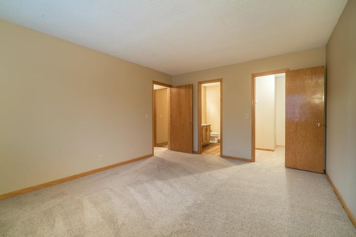 Interiors- Large master bedroom with bathroom attached at Oakwood Trail Apartments in Omaha Nebraska.jpg