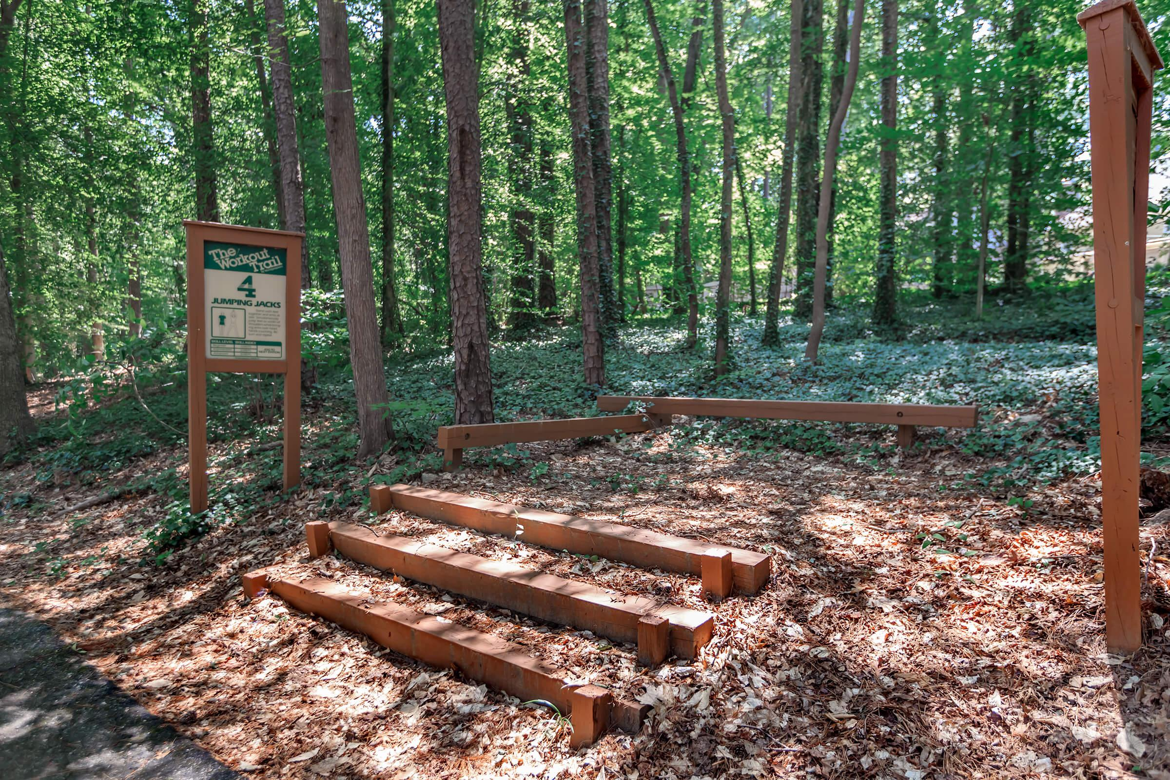 a wooden bench next to a forest