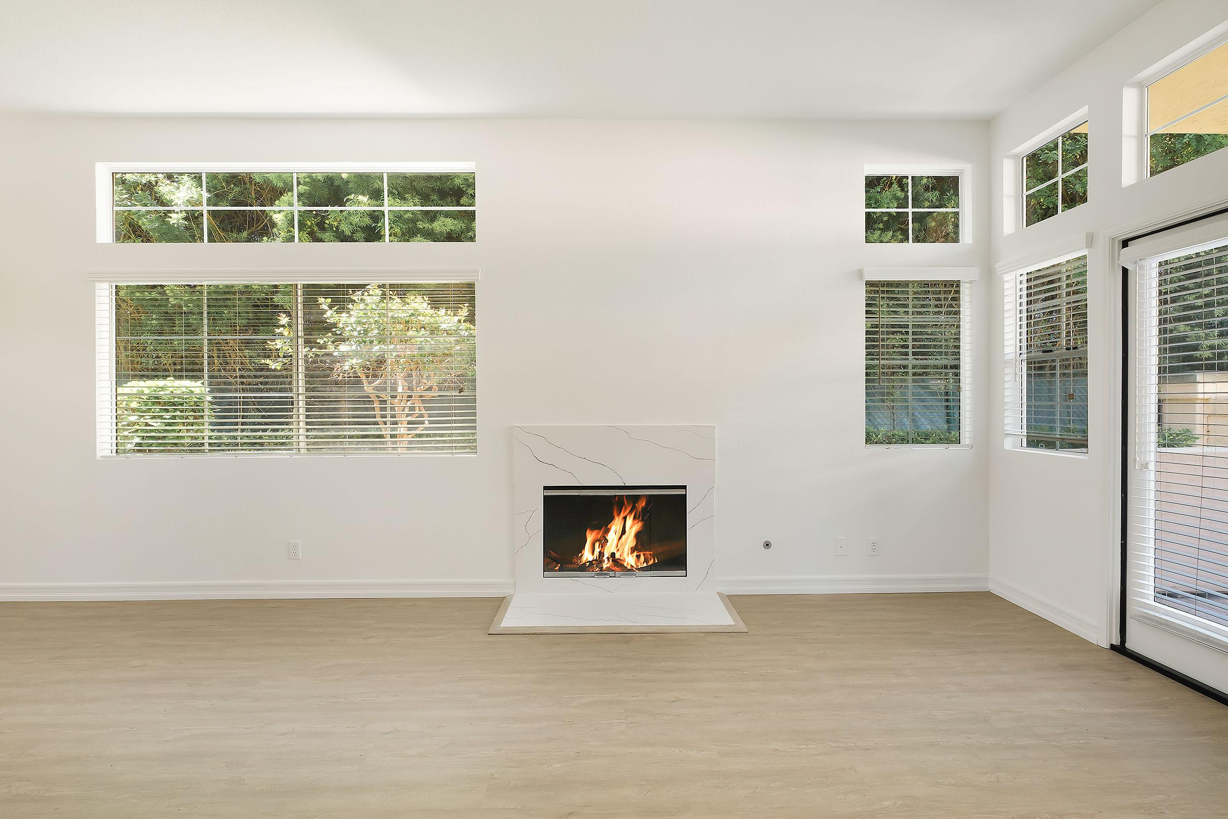 a living room with a fireplace and a large window
