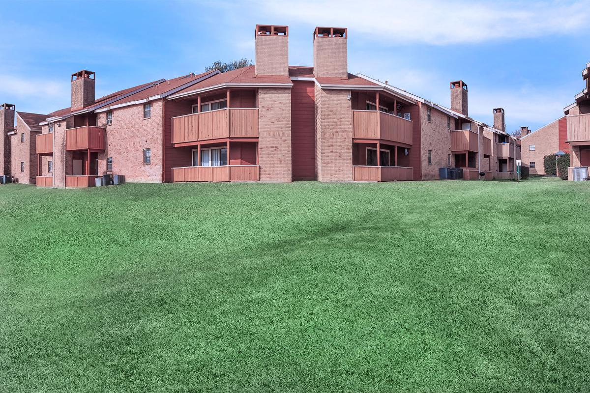 a large brick building with a grassy field