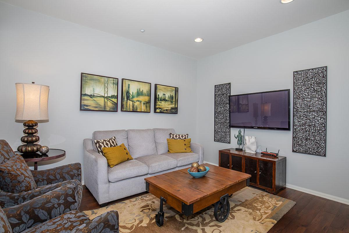 Living room with recessed lighting and plank flooring