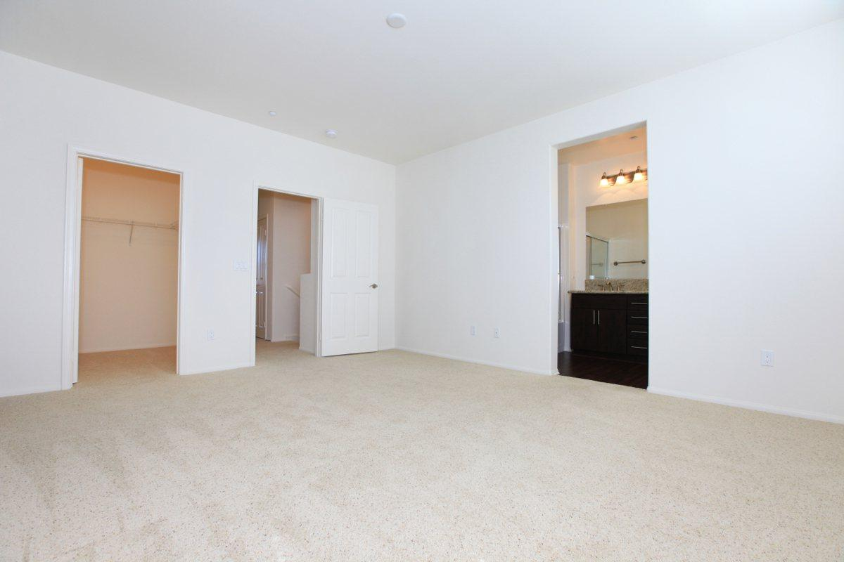 Bedroom with plush carpeting and walk-in closets