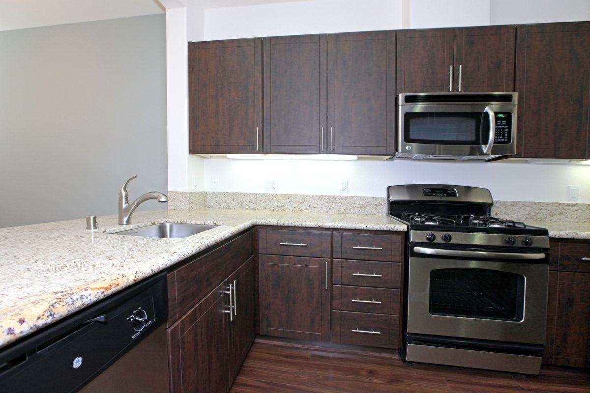Stainless steel appliances with granite countertops and espresso cabinets