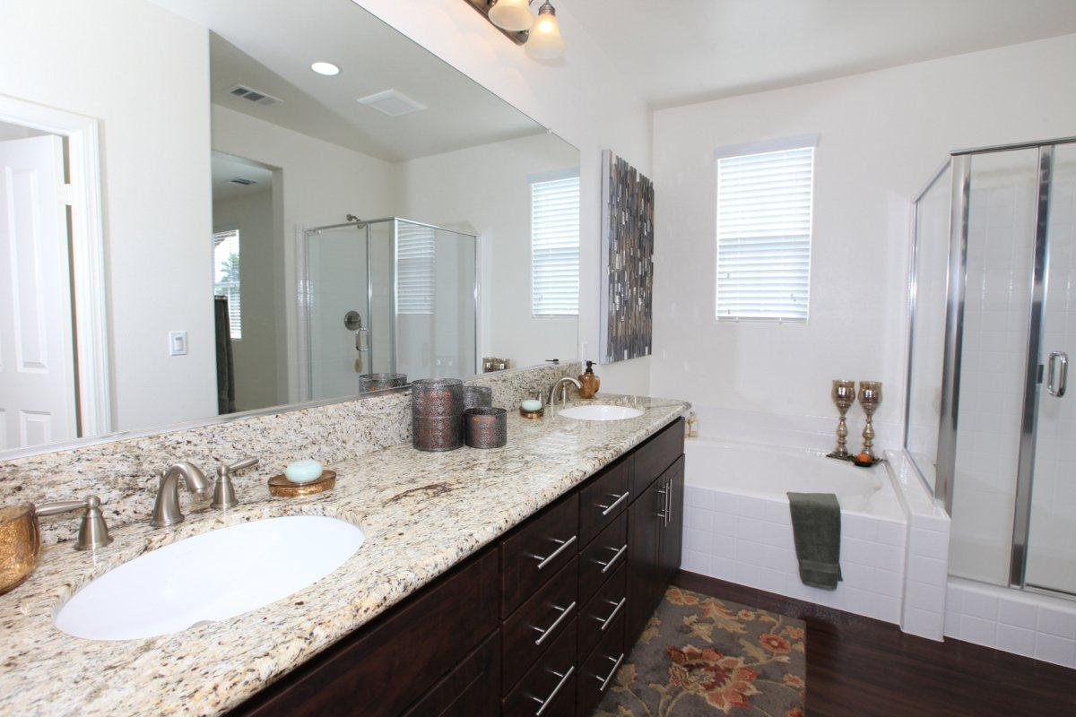 Bathroom with double sink vanity, stand alone shower, and bath tub