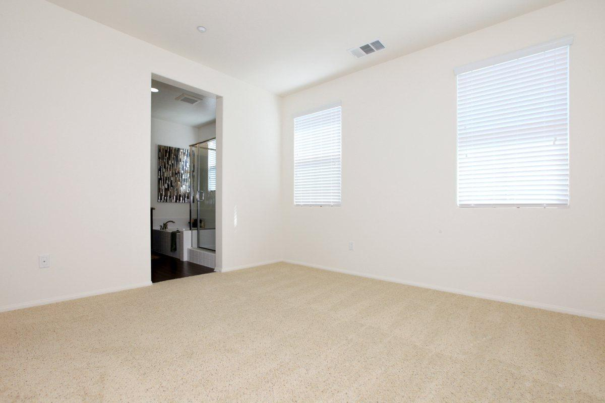 Bedroom with plush carpeting and attached bathroom