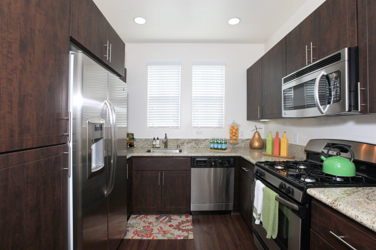 Stainless steel appliances with espresso cabinets and granite countertops