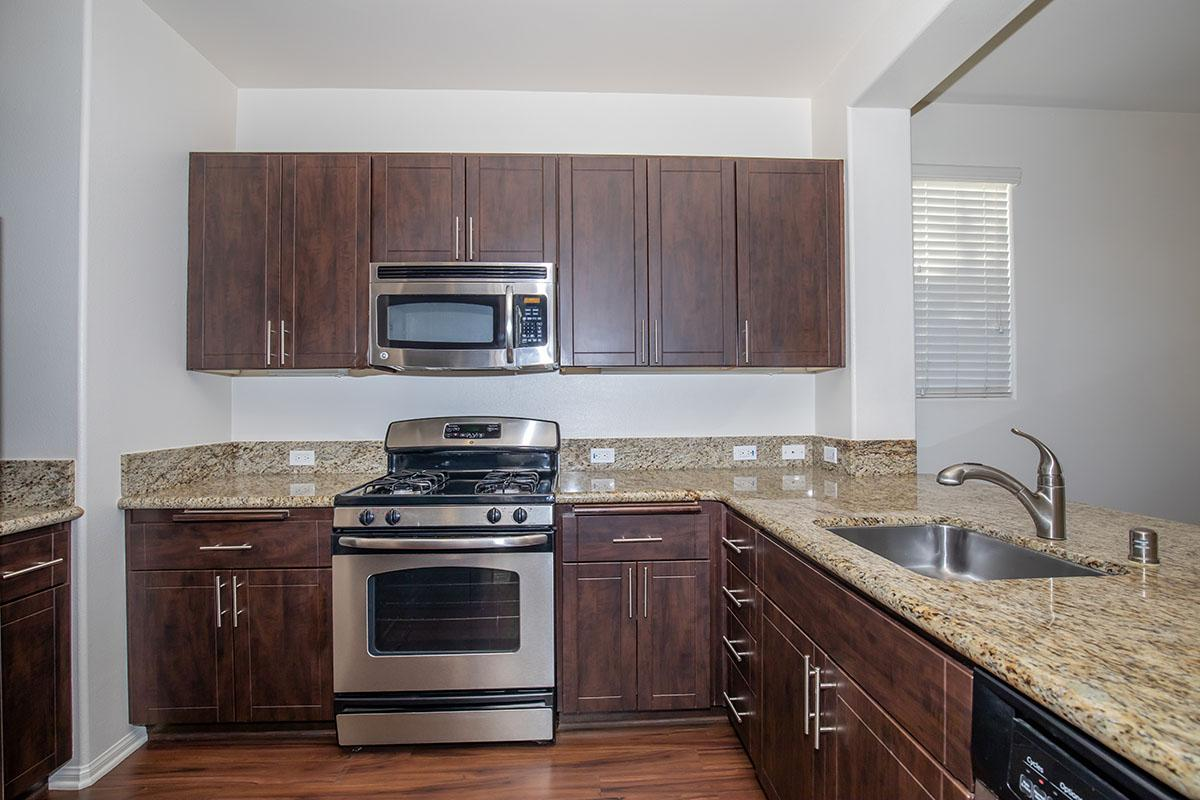 Fully-equipped kitchen and with granite countertops and plank flooring