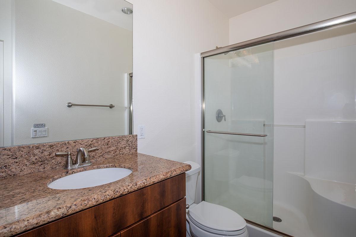Bathroom with granite countertop and glass shower door