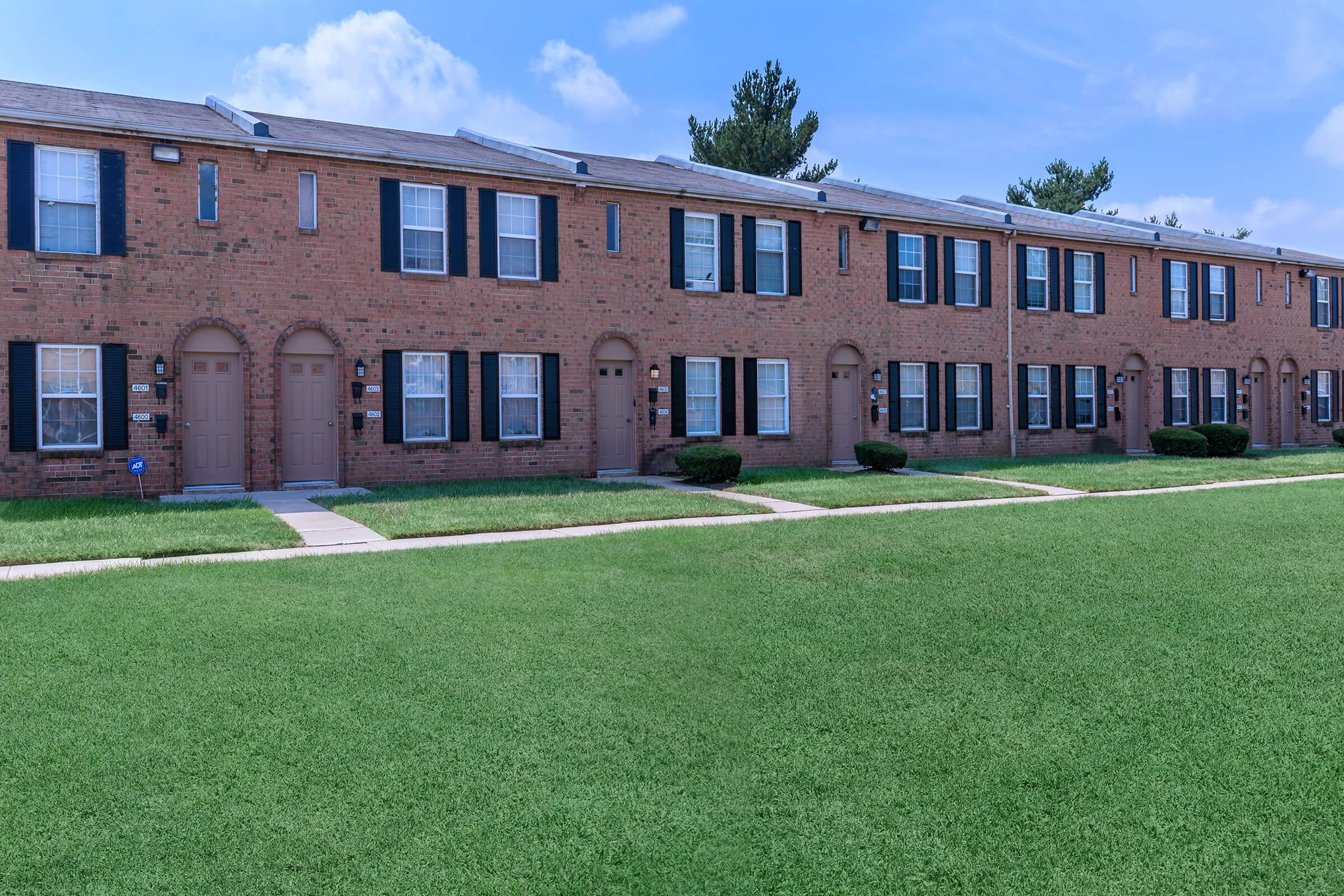 a large brick building with green grass
