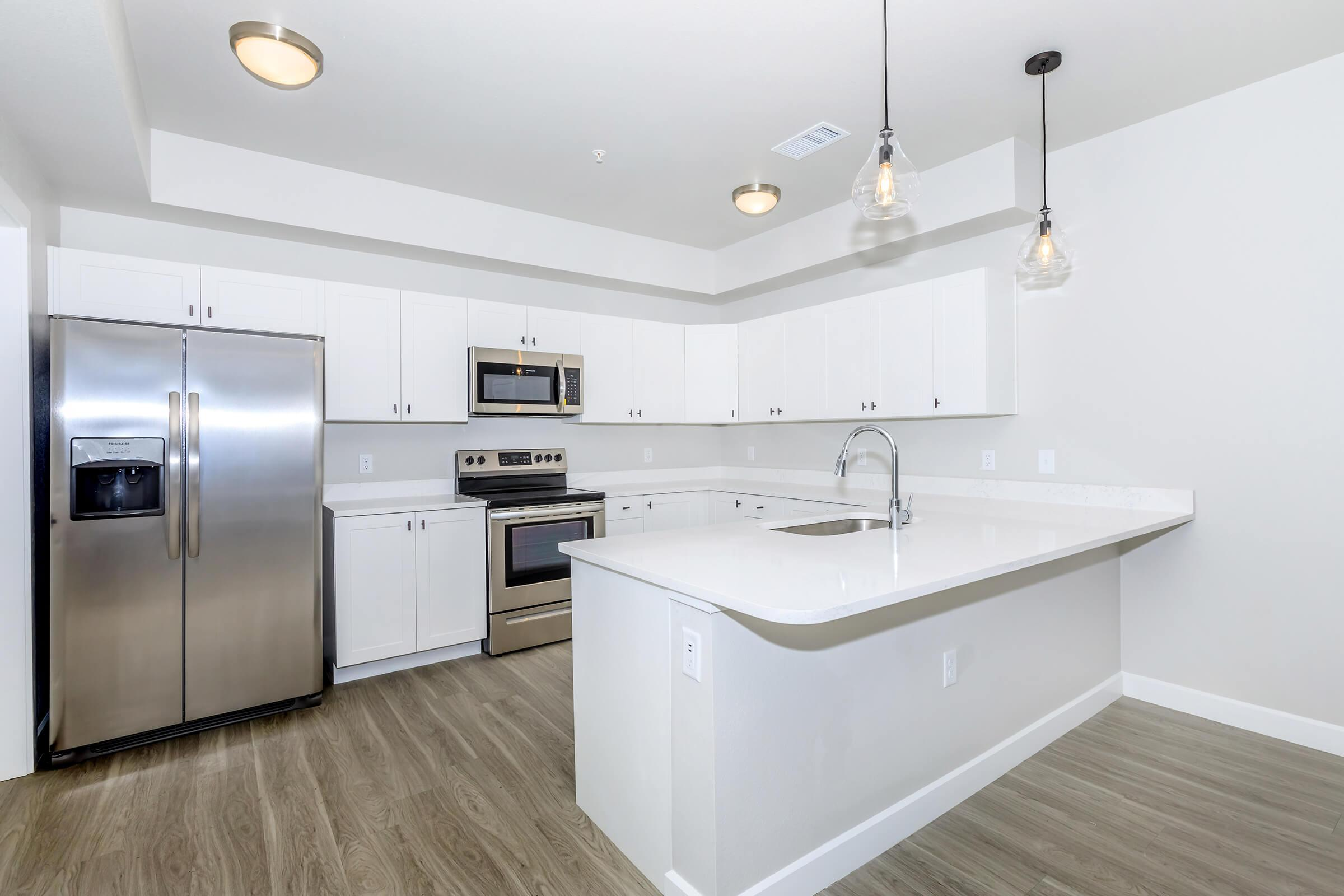 a large kitchen with white cabinets and a sink