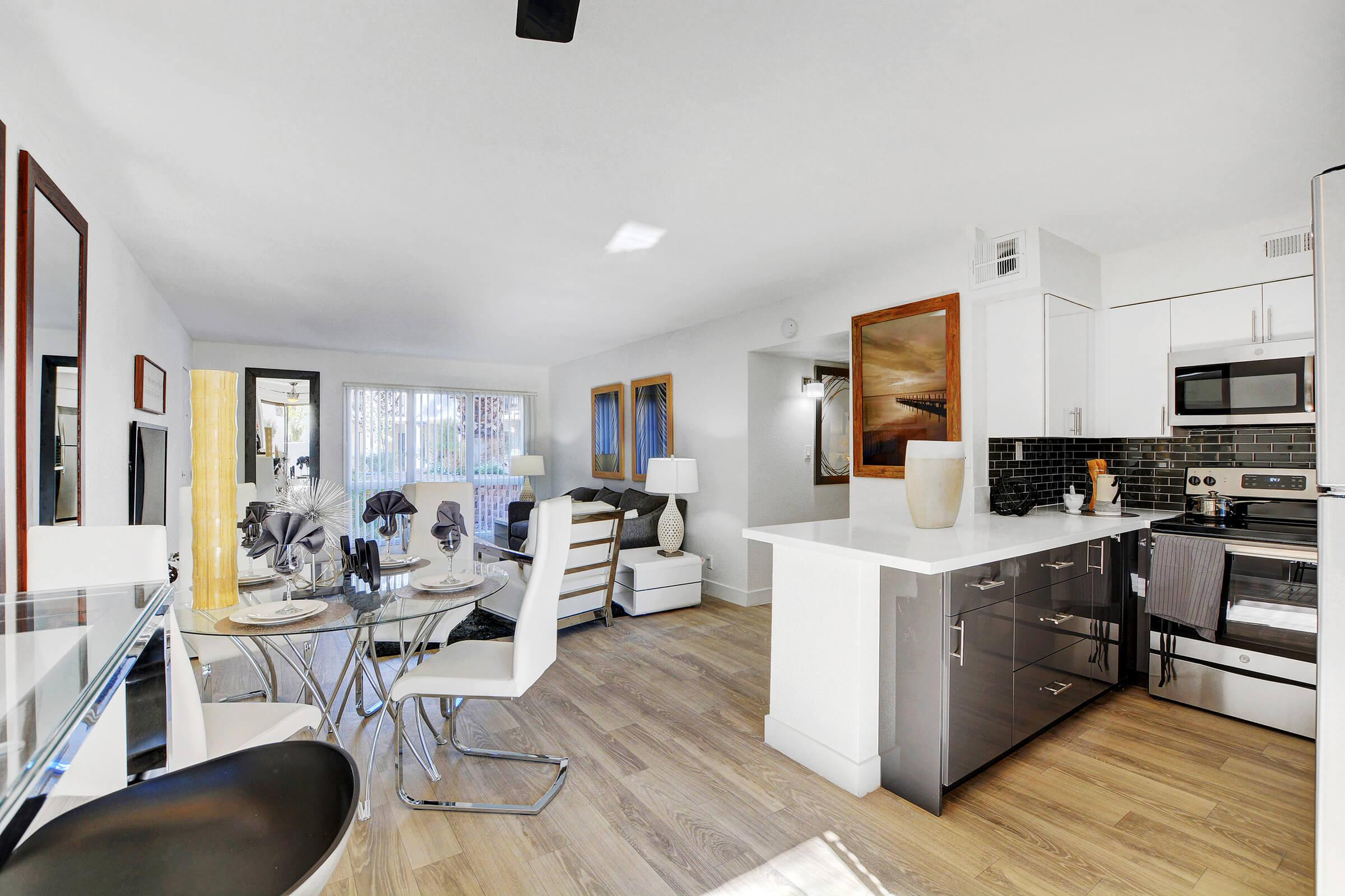 a living room filled with furniture and a counter in a kitchen