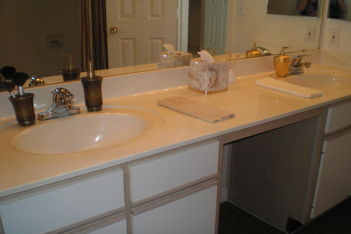 a white sink sitting under a mirror