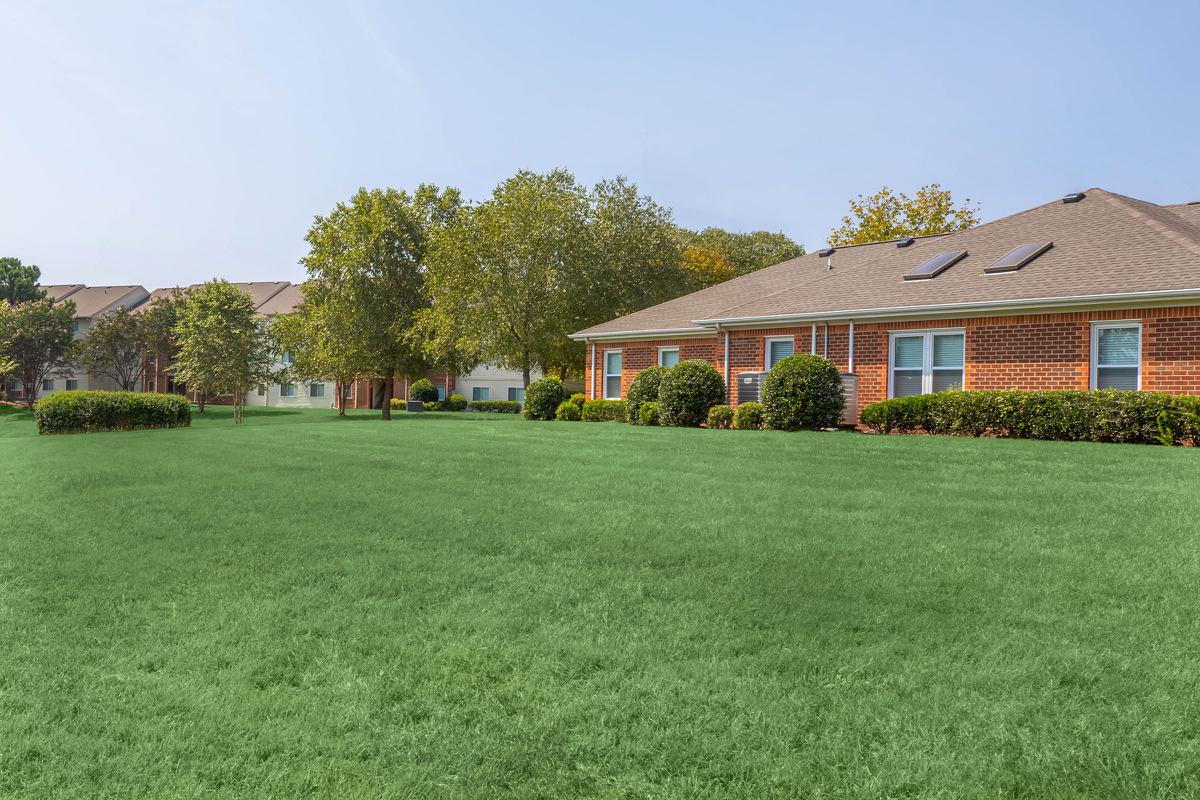 a large green field in front of a house