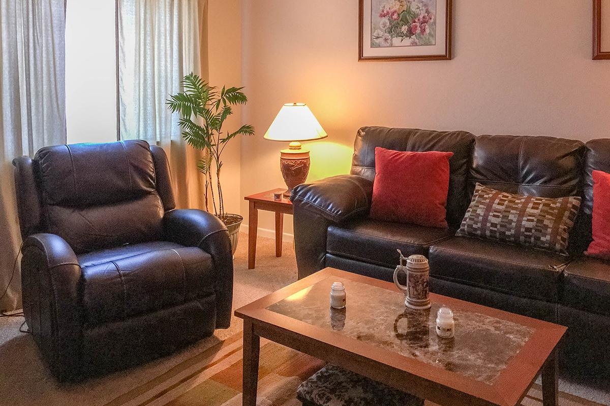 a brown leather couch in a living room filled with furniture and a lamp