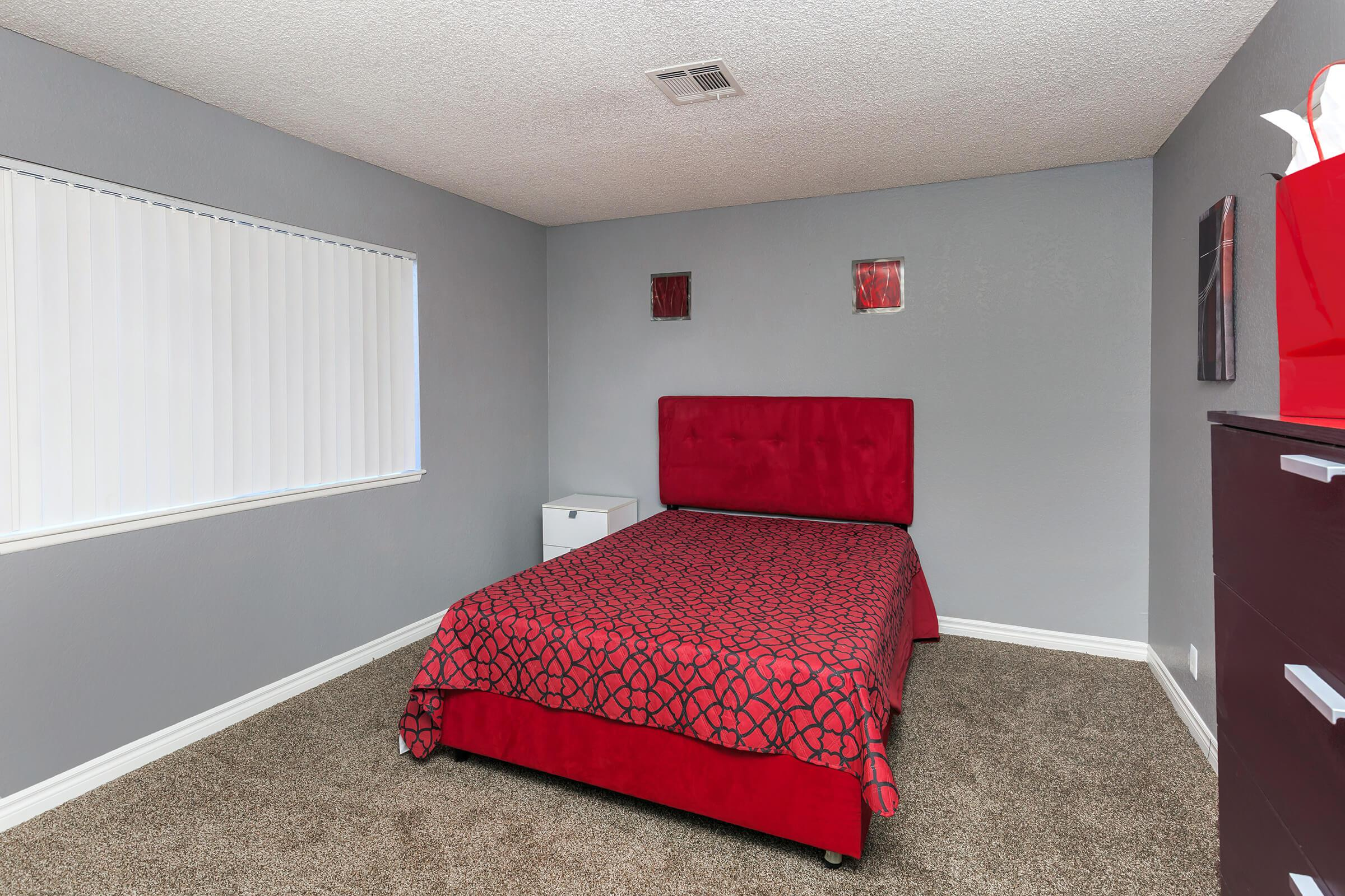 a bedroom with a red blanket