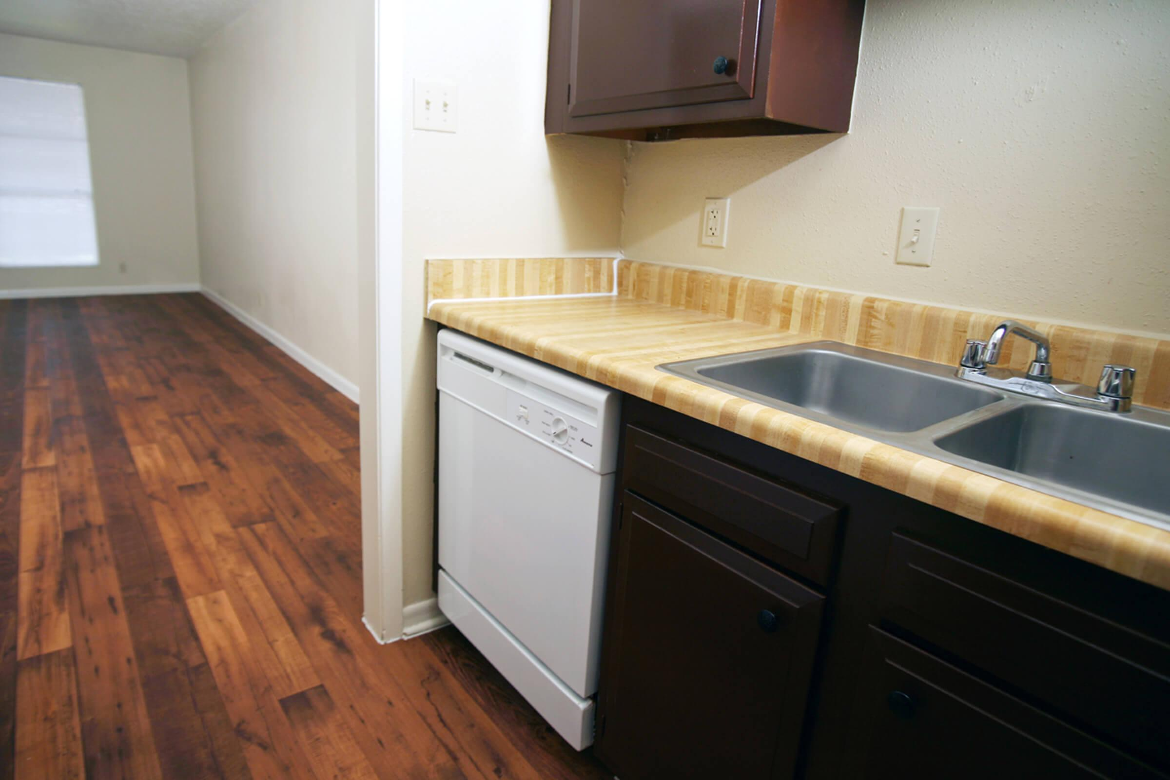 a kitchen with a sink and a wood floor
