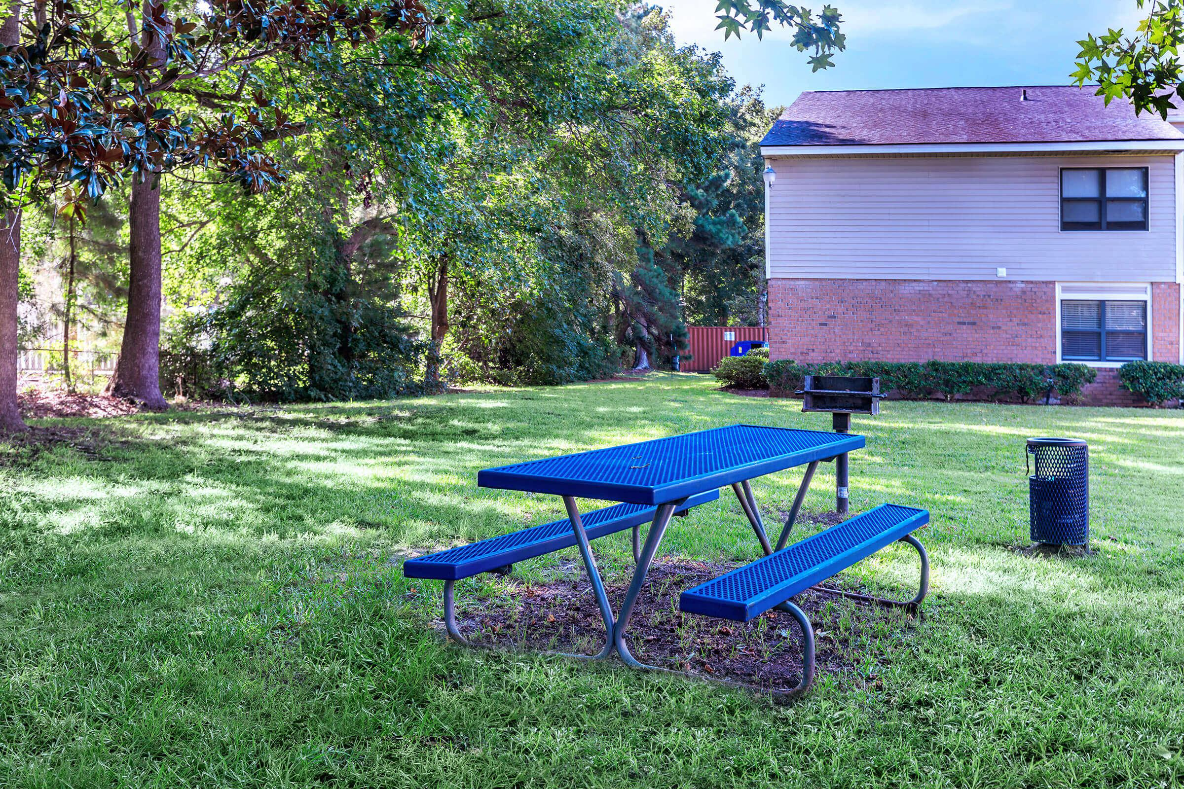 an empty park bench sitting in front of a picnic table