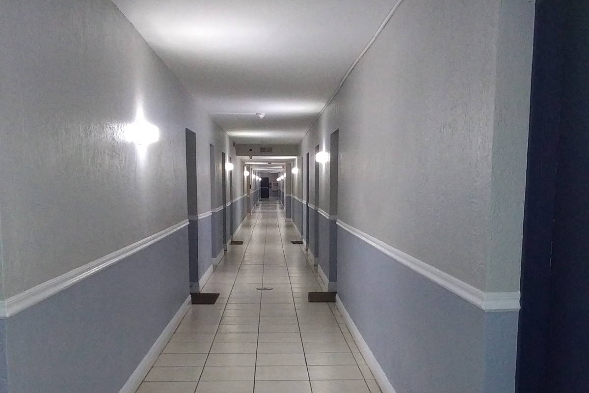 a narrow hallway with a tiled floor
