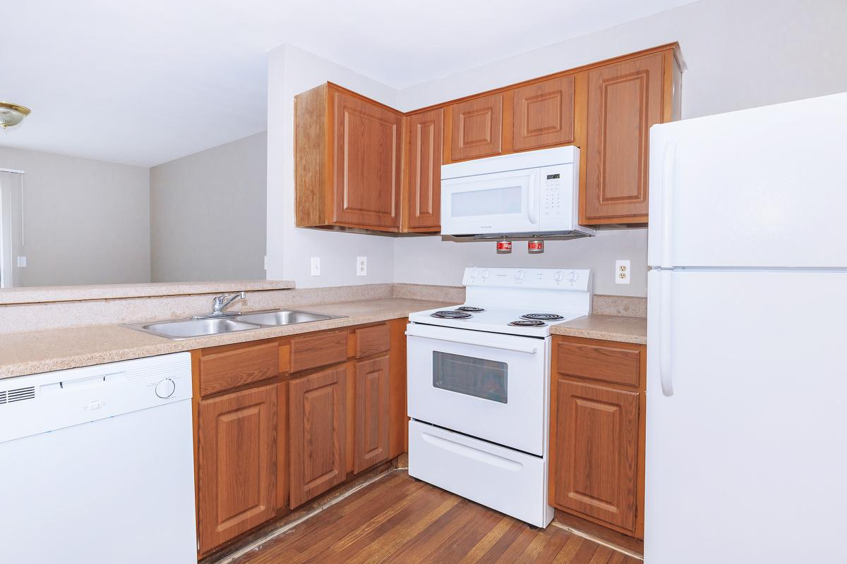 a kitchen with white cabinets and stainless steel appliances and wooden cabinets