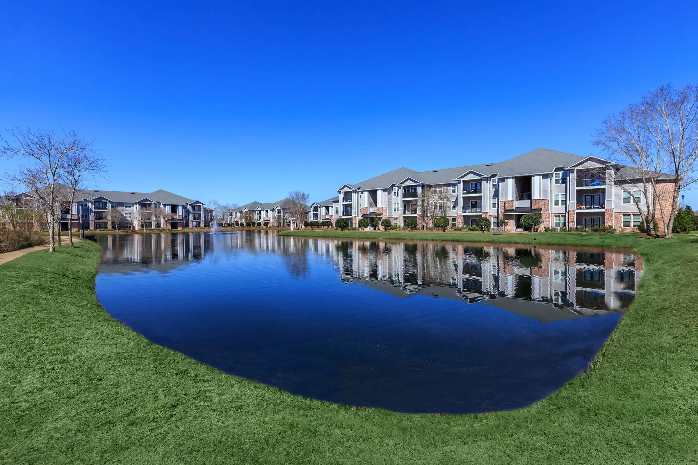 a large lawn in front of a body of water