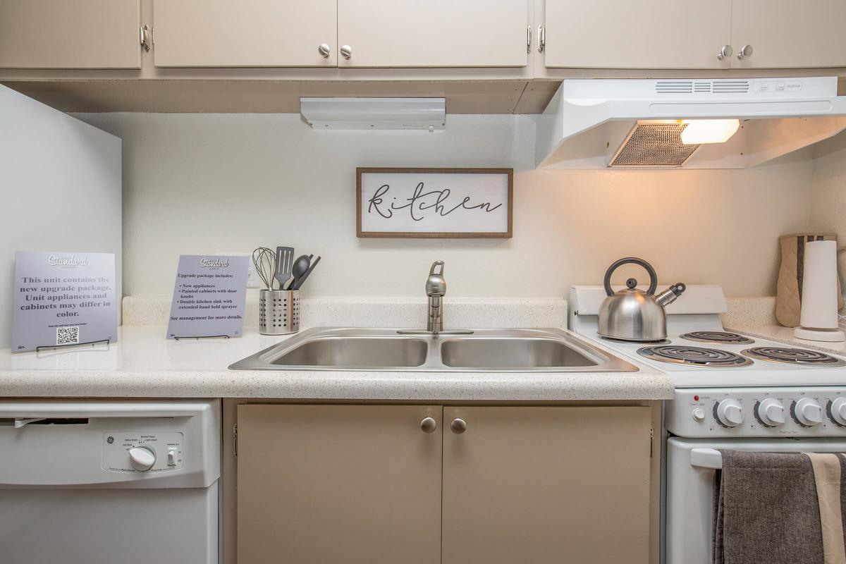 a kitchen with a white stove top oven sitting next to a sink