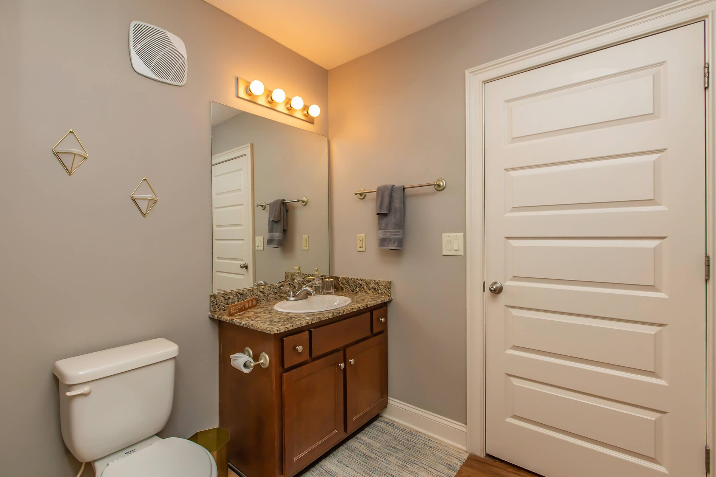 a bedroom area with a sink and a mirror