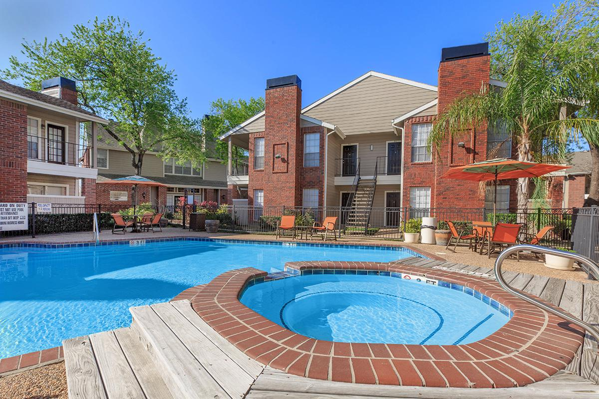 a house with a pool in front of a brick building