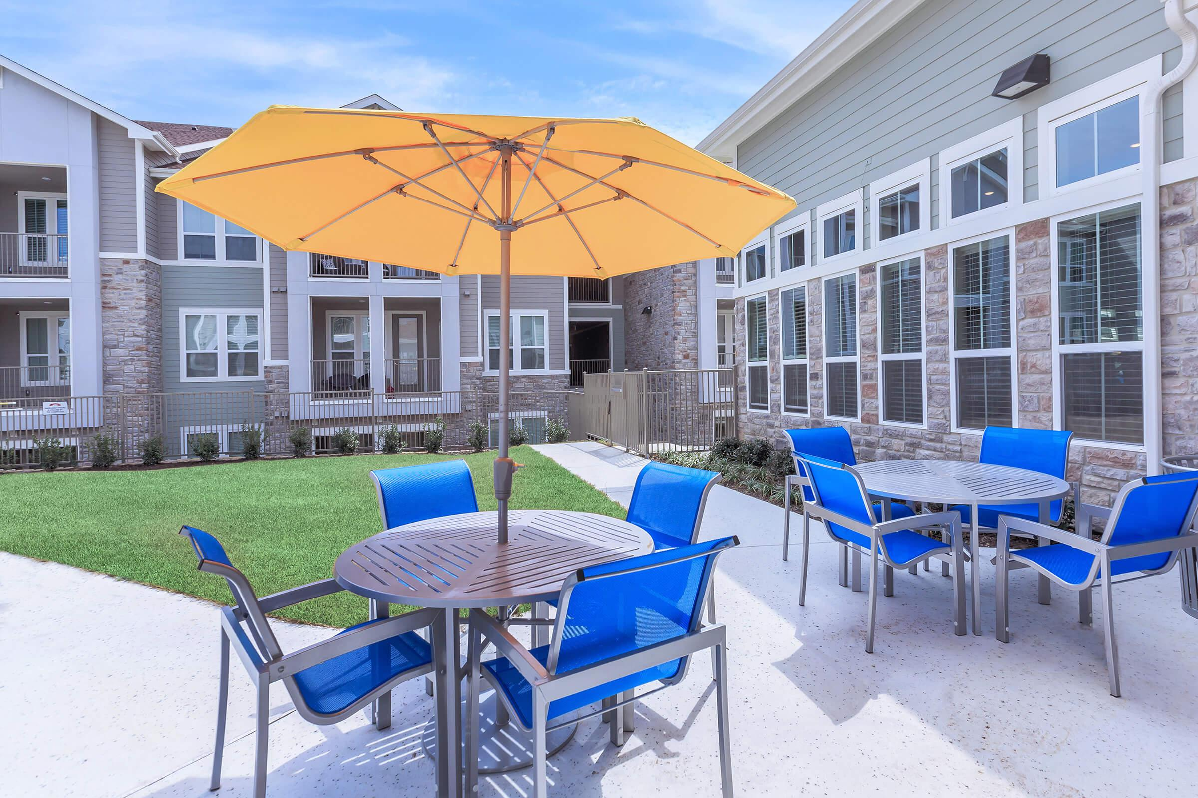 a group of lawn chairs sitting on a chair with a blue umbrella