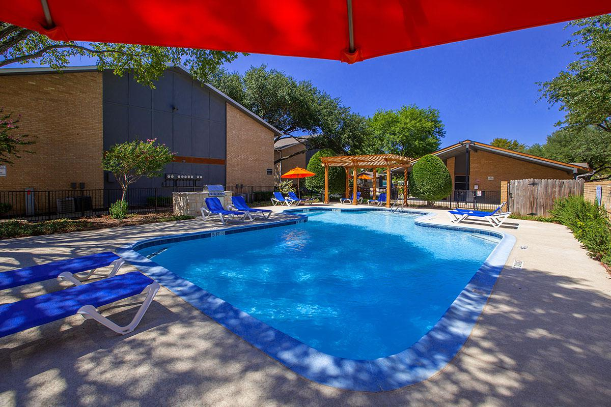 a pool with a blue umbrella