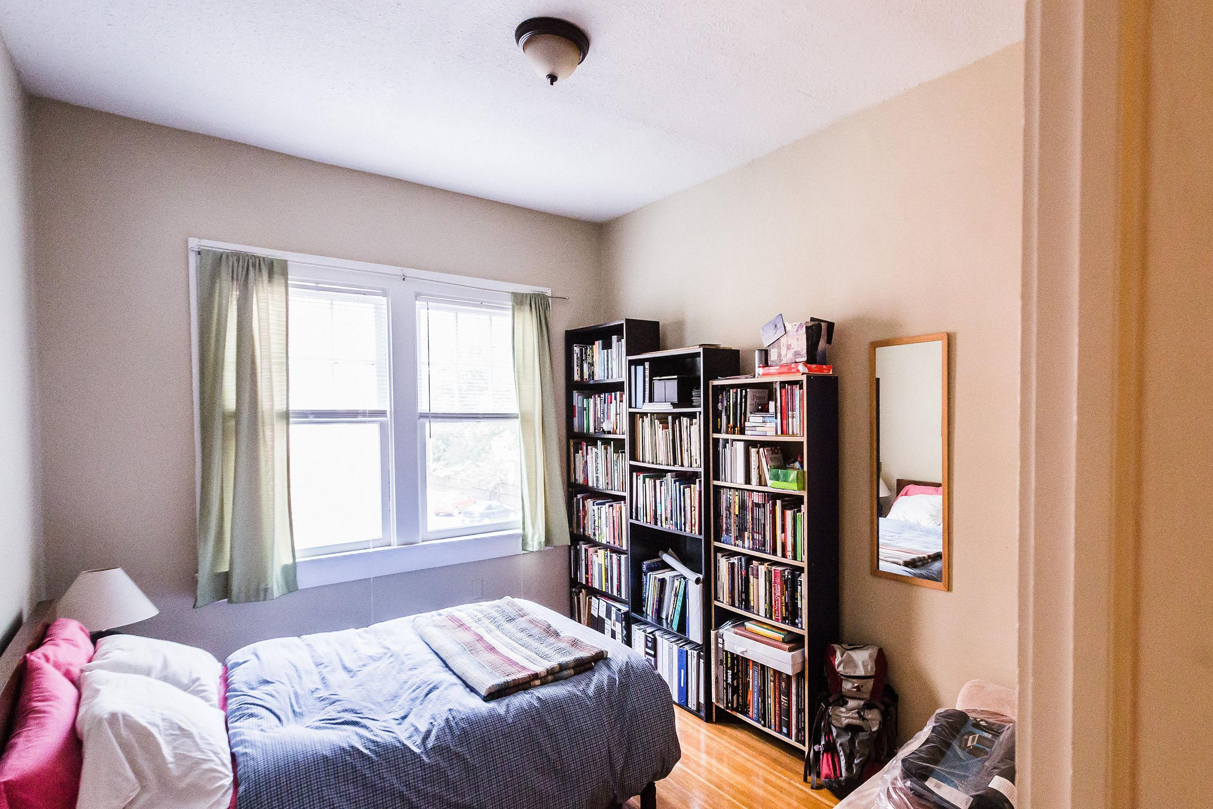 a bedroom with a book shelf