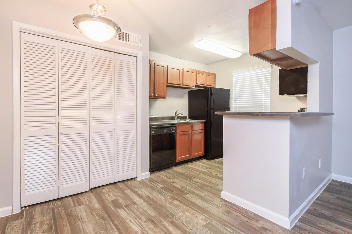 a kitchen with wooden cabinets and a refrigerator