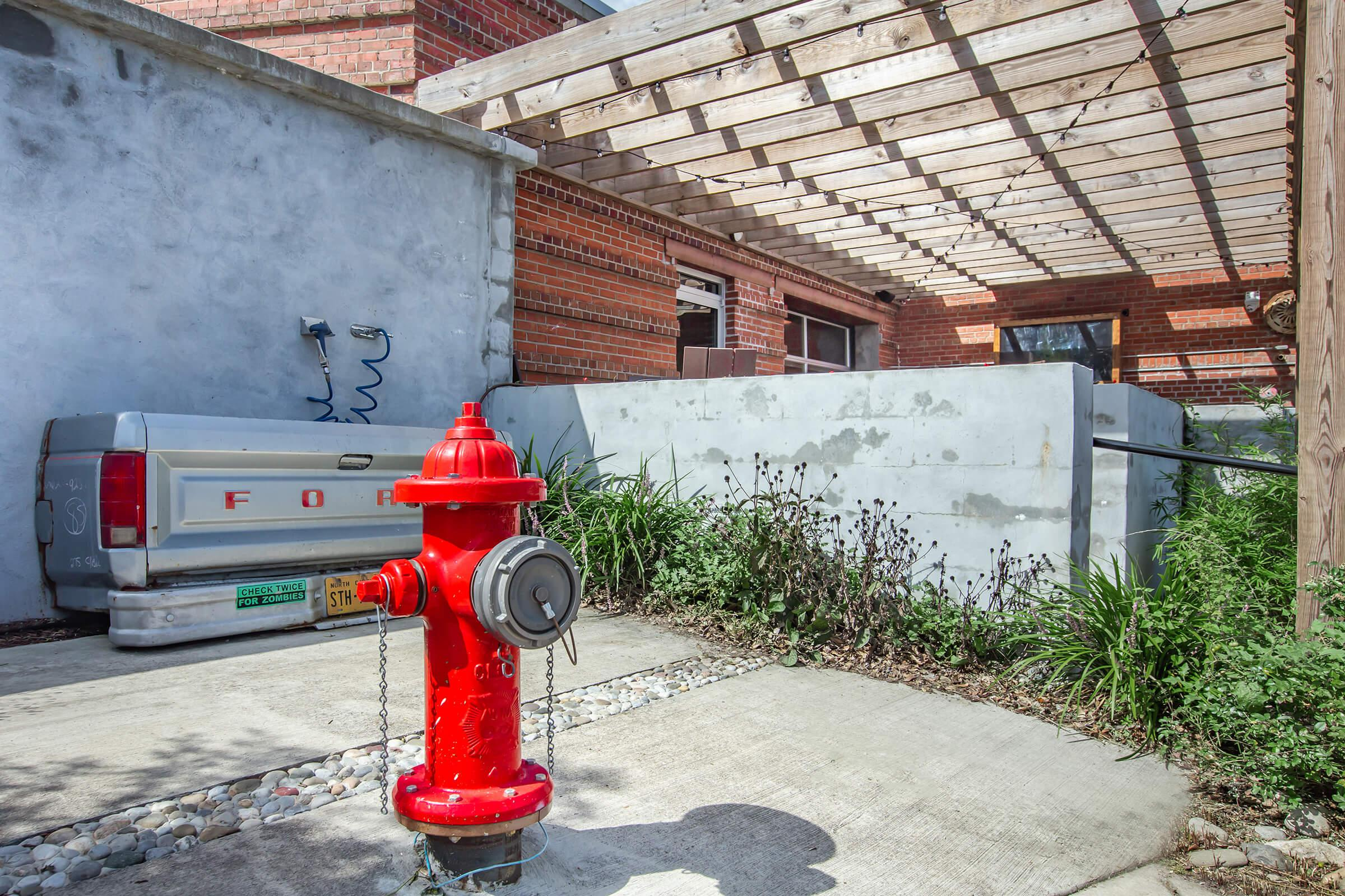 a red fire hydrant sitting on the side of a building