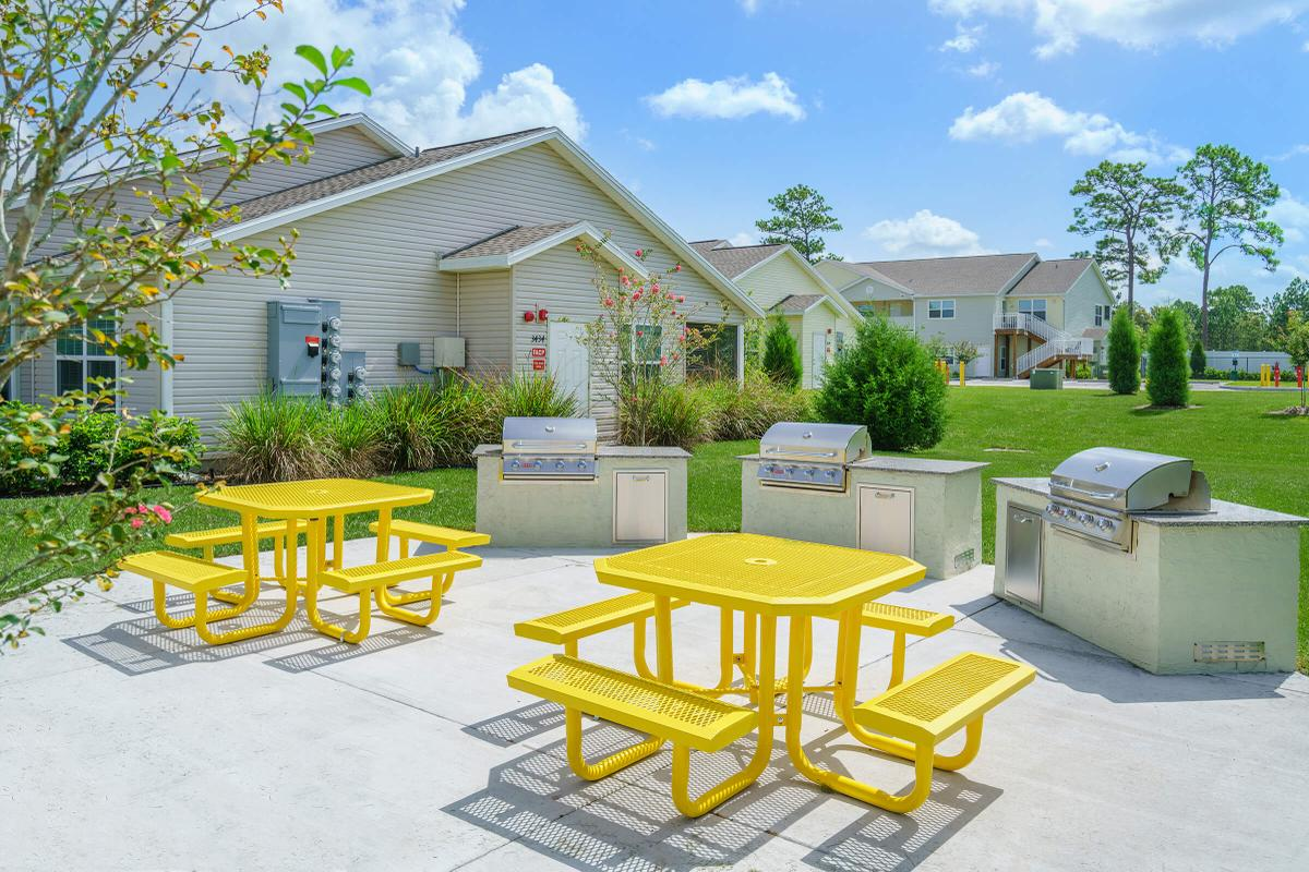 a yellow house in the middle of a park bench