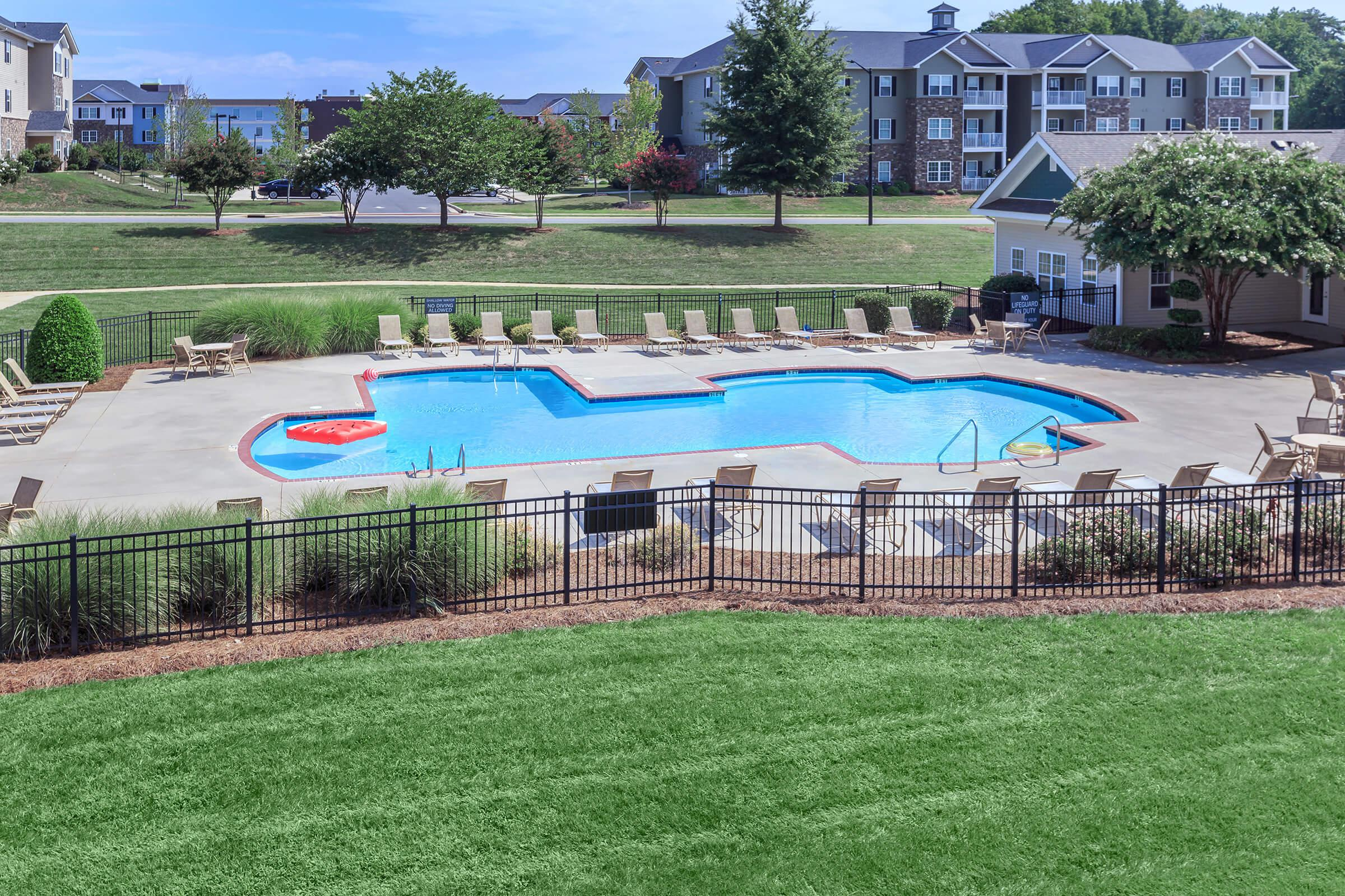 a large lawn in front of a pool