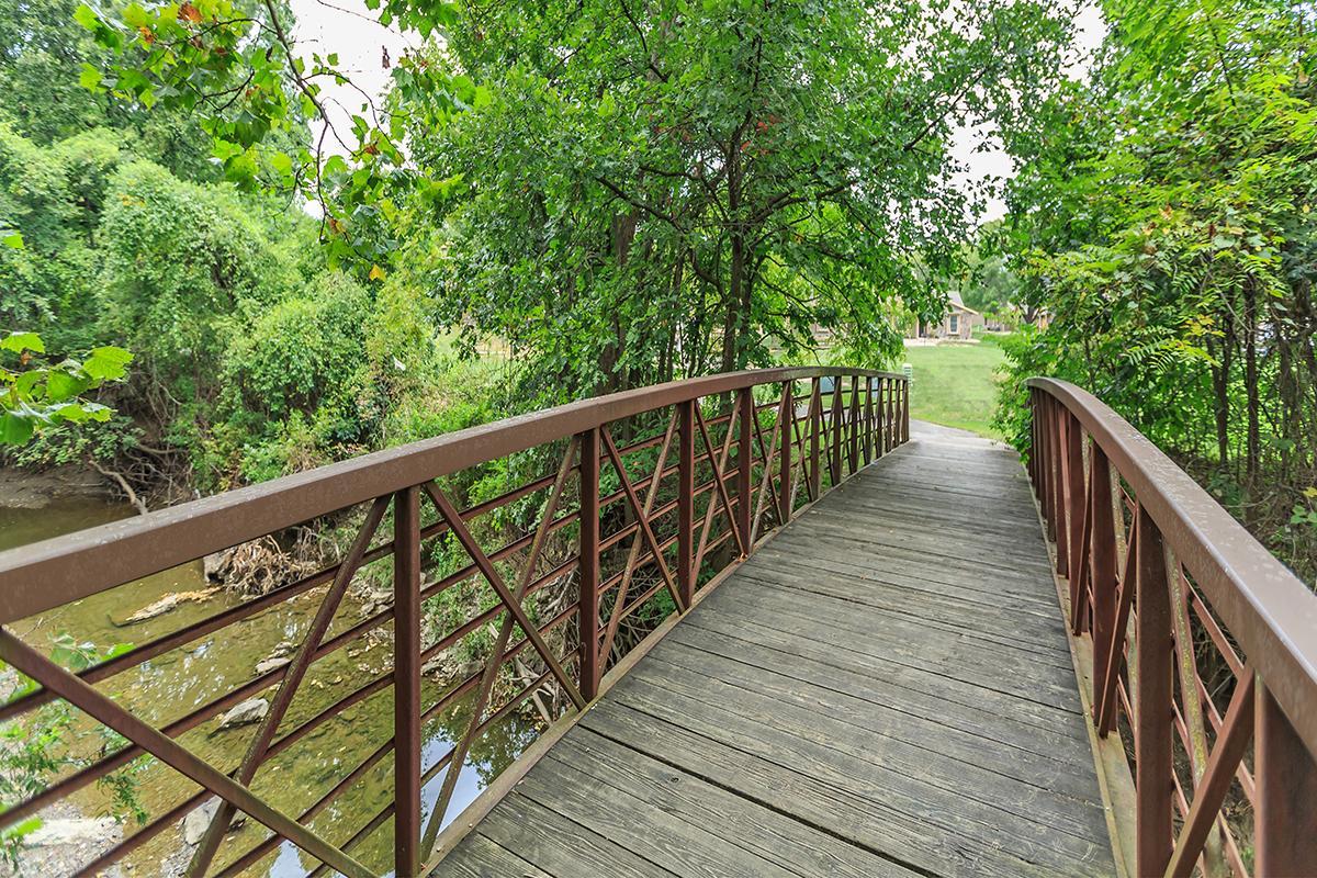 a wooden bench near a bridge
