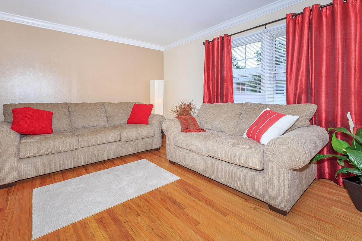 a living room filled with furniture and a red curtain