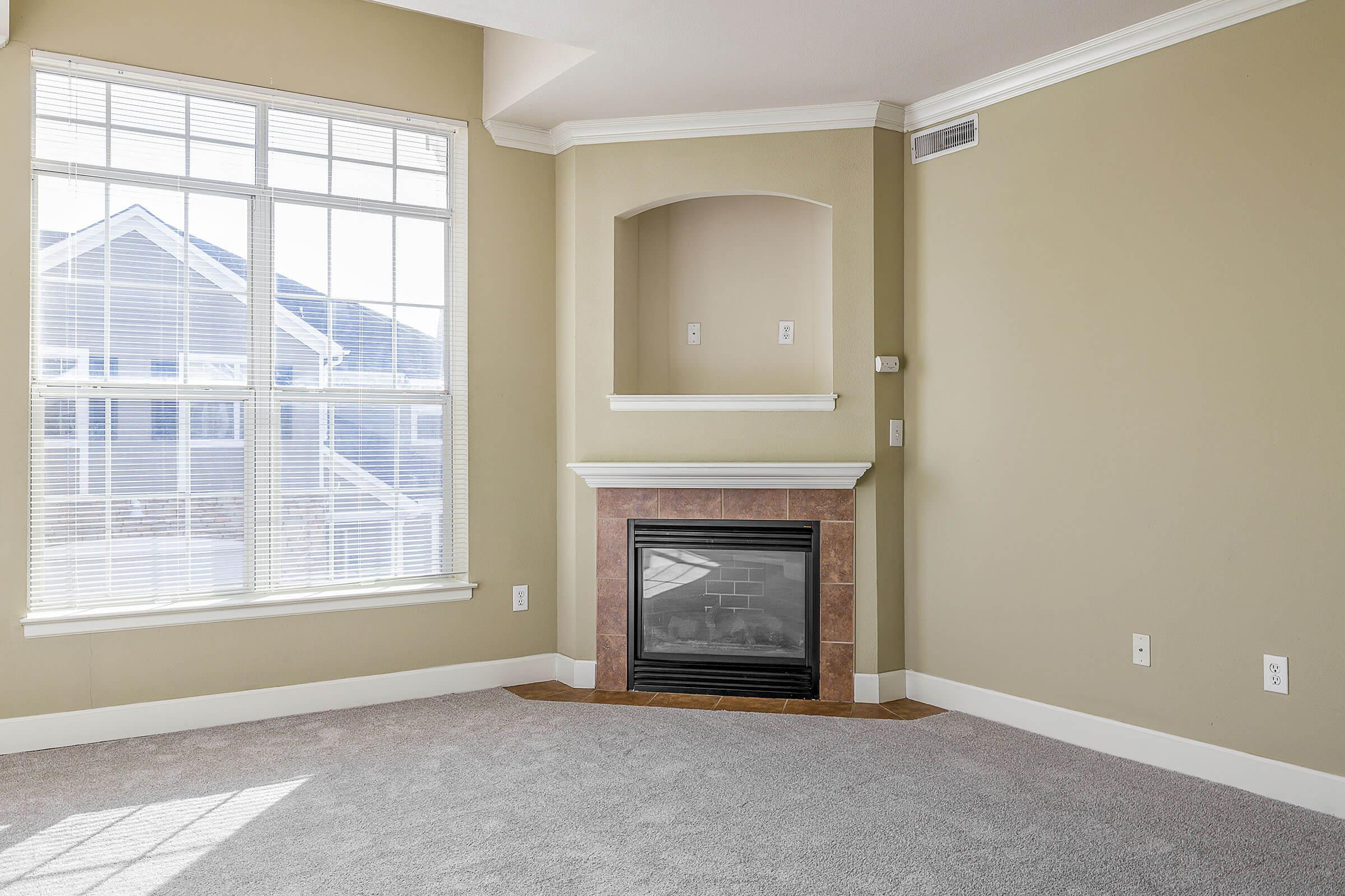 a room with a fireplace and a large window