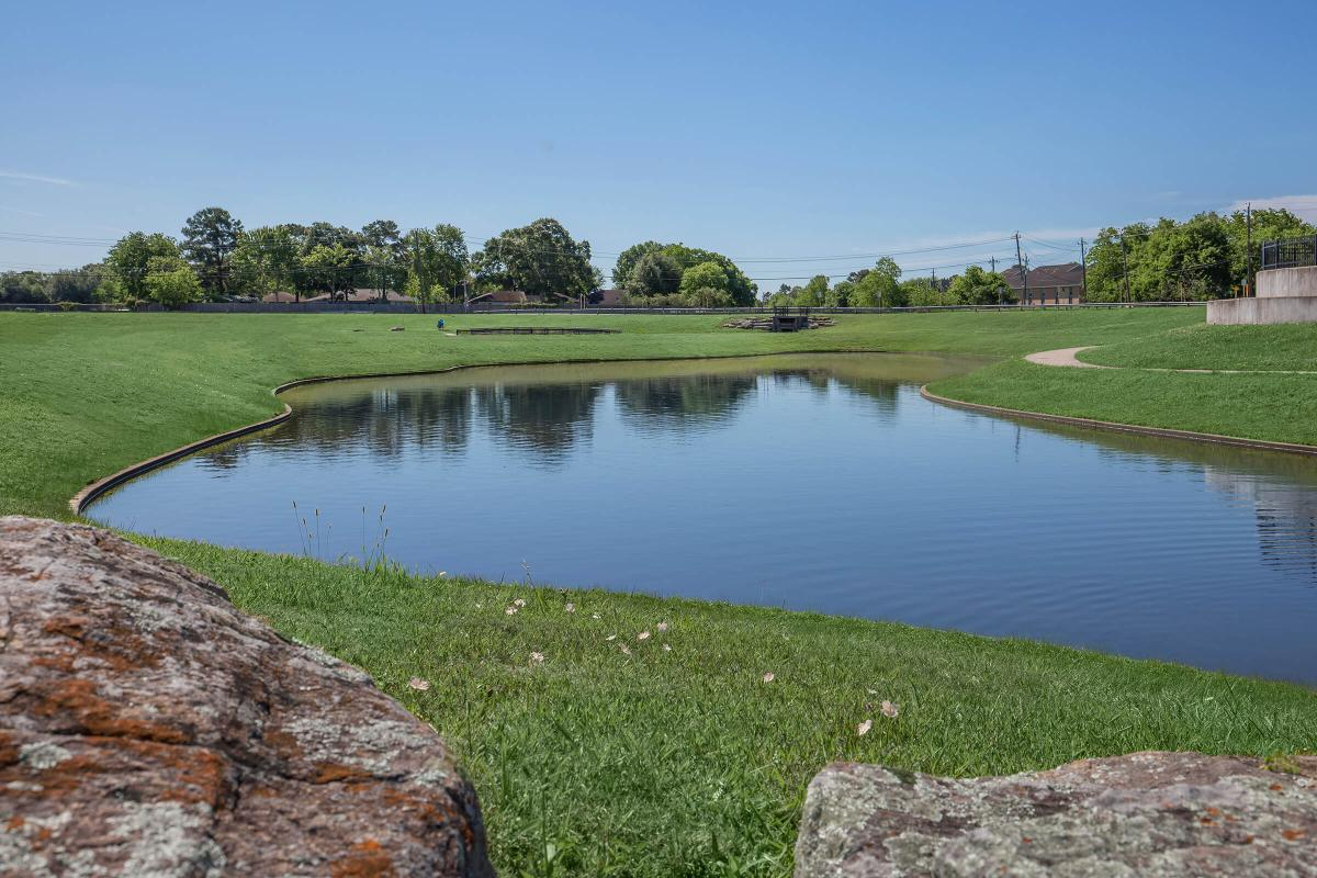 a pond next to a body of water with The Golf Club at Harbor Shores in the background